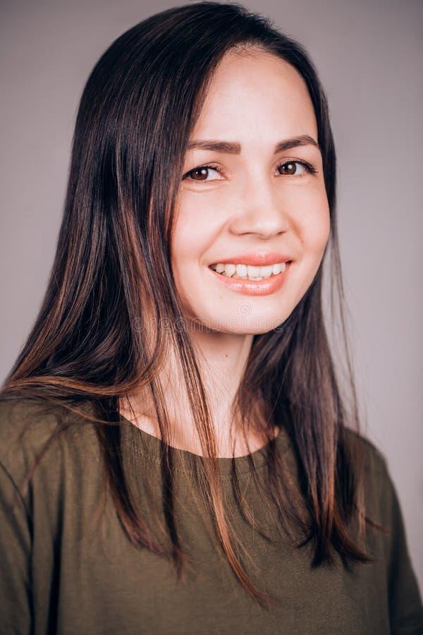 Nahaufnahmeporträt einer jungen attraktiven Brunettefrau mit der sauberen gesunden Gesichtshaut, die mit einem Lächeln der Kamera lizenzfreie stockfotos