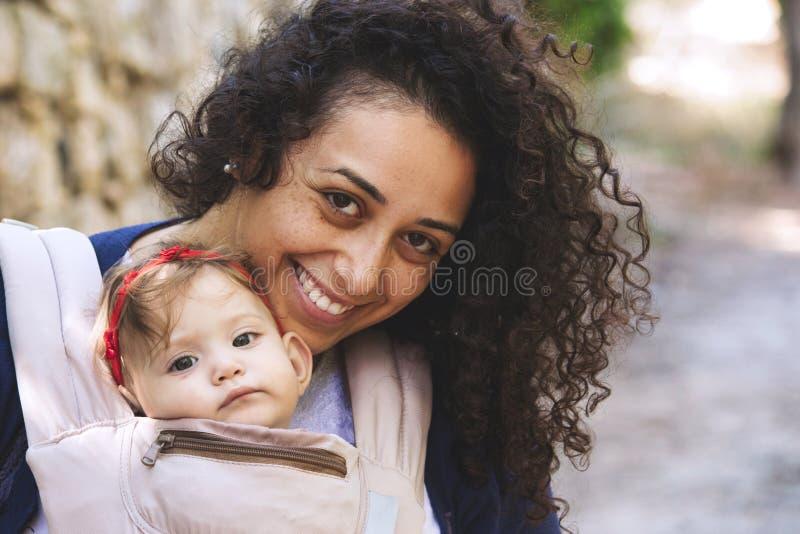 Nahaufnahmeporträt einer jungen attraktiven Mutter, die ein Baby in einer Riemenfördermaschine trägt stockfoto