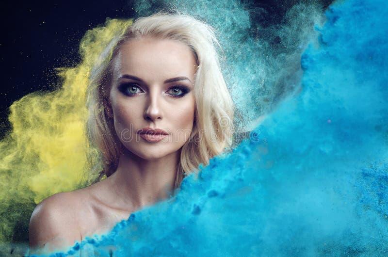 Nahaufnahmeporträt einer reizend blonden Dame unter blauer und gelber Pulverwolke stockfotografie