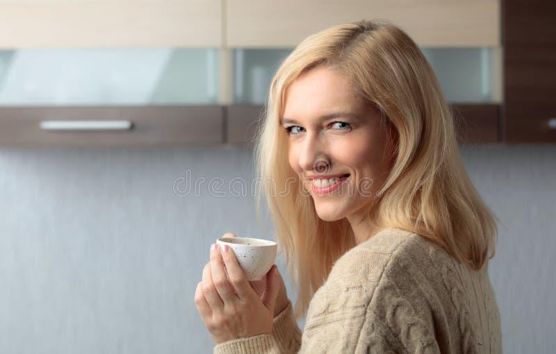 Nahaufnahmeporträt einer schönen mittleren Altersfrau mit Tasse Kaffee stockfotografie