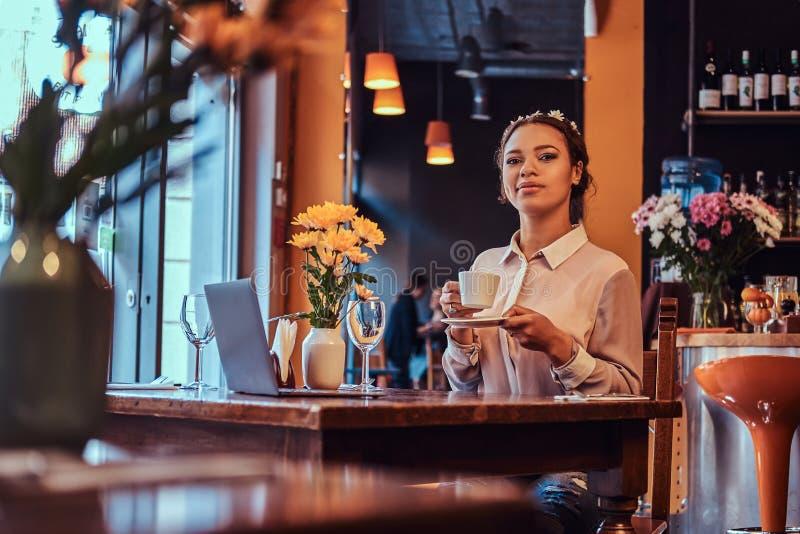 Nahaufnahmeporträt einer schönen schwarz-enthäuteten Frau, die ein Blusen- und Blumenstirnband, Grifftasse kaffee in a trägt stockbilder