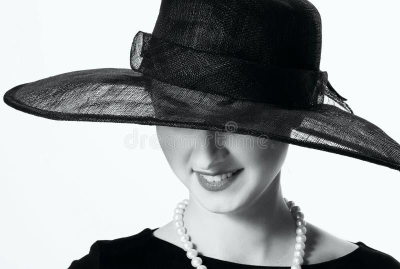 Nahaufnahmeporträt einer Schönheit in einem schwarzen Hut in Retro- s stockbild