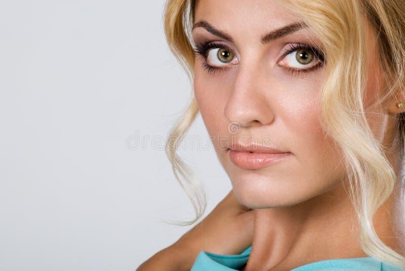Nahaufnahmeporträt einer Schönheit mit der sauberen Haut, welche die Kamera lokalisiert betrachtet stockbilder