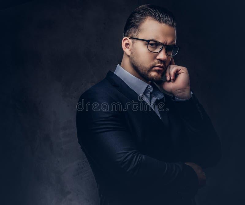 Nahaufnahmeporträt eines durchdachten stilvollen Geschäftsmannes mit ernstem Gesicht in einem eleganten Gesellschaftsanzug und in lizenzfreies stockfoto