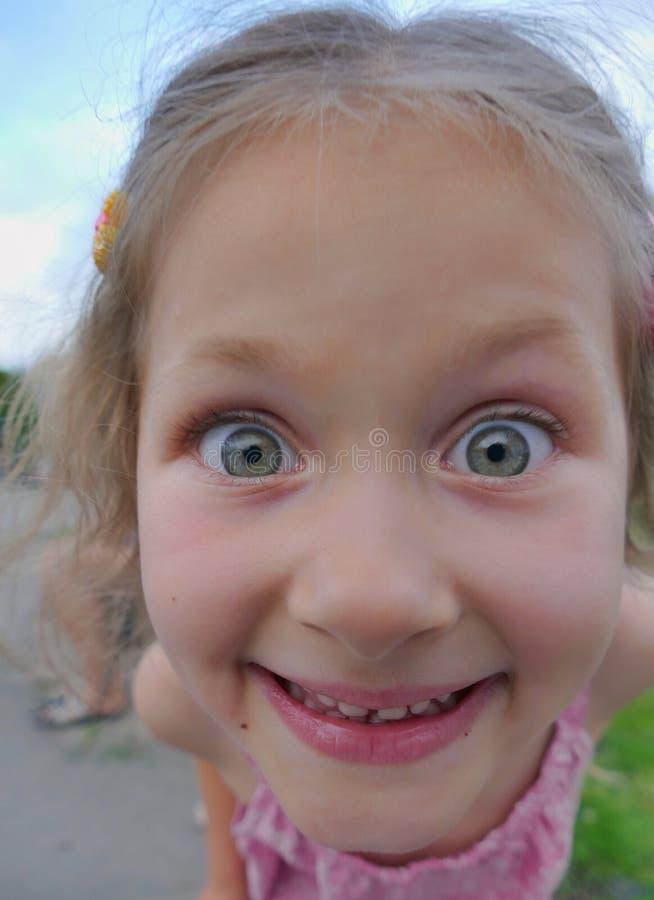 Nahaufnahmeporträt eines frechen lustigen kleinen Mädchens, das mit Interesse dem Kameraobjektiv betrachtet stockbilder