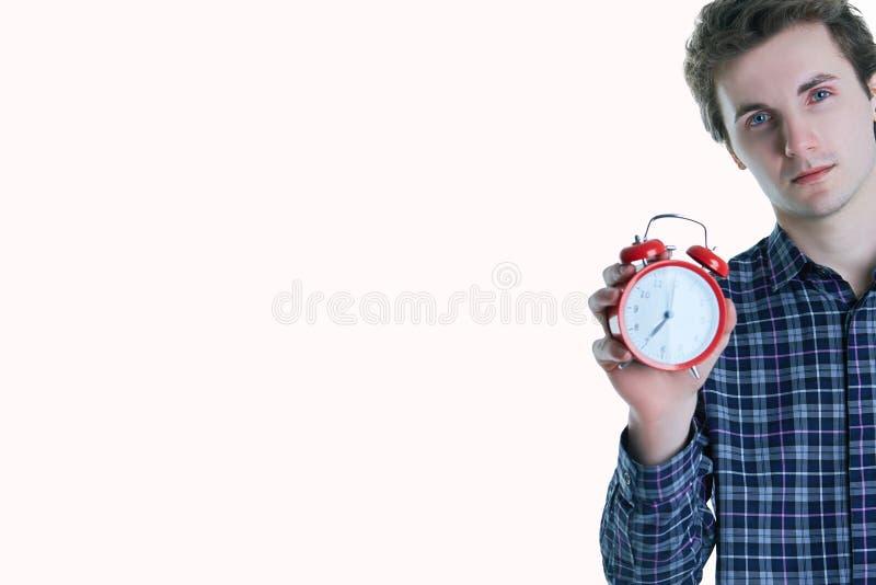 Nahaufnahmeporträt eines gestörten jungen Mannes, der Wecker lokalisiert über weißem Hintergrund hält lizenzfreies stockbild