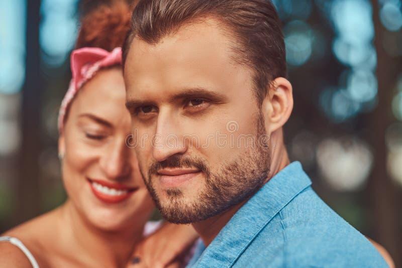 Nahaufnahmeporträt eines glücklichen attraktiven Paares, streichelnd während draußen datieren in einen Park stockfoto