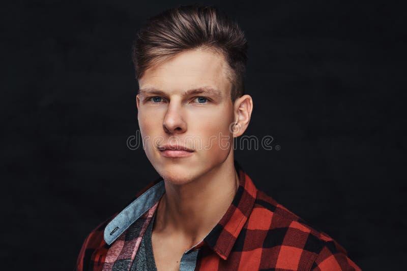 Nahaufnahmeporträt eines hübschen jungen Mannes in einem Vlieshemd, werfend an einem Studio auf stockfoto
