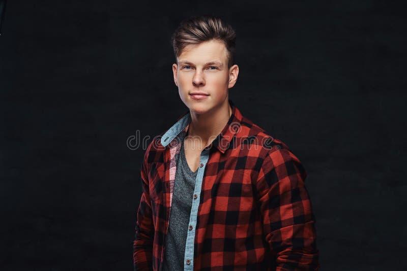 Nahaufnahmeporträt eines hübschen jungen Mannes in einem Vlieshemd, werfend an einem Studio auf lizenzfreies stockbild