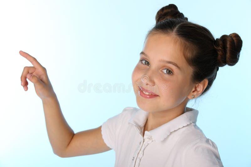 Nahaufnahmeporträt eines hübschen Kindermädchens lächelt und zeigt mit ihrem Finger stockbild