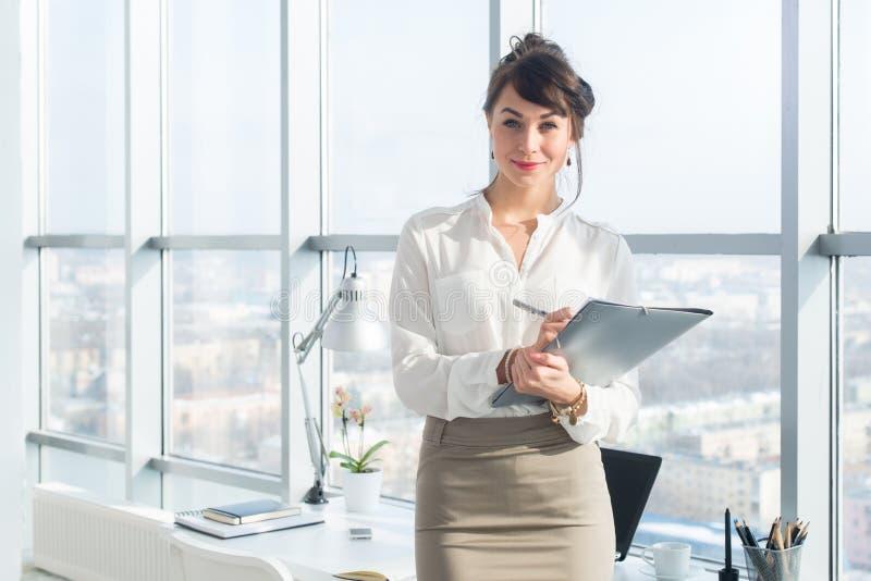 Nahaufnahmeporträt eines jungen überzeugten weiblichen Bürovorstehers an ihrem Arbeitsplatz, bereiten für das Handeln von Geschäf lizenzfreies stockbild