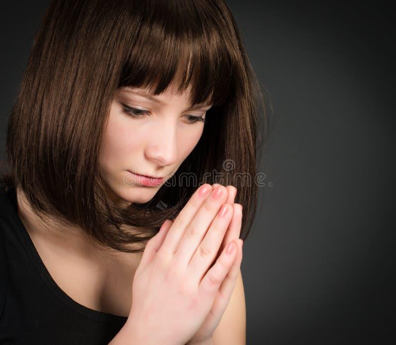 Nahaufnahmeporträt eines jungen Brunettefrauenbetens Betendes Mädchen auf dunklem Hintergrund stockfotos