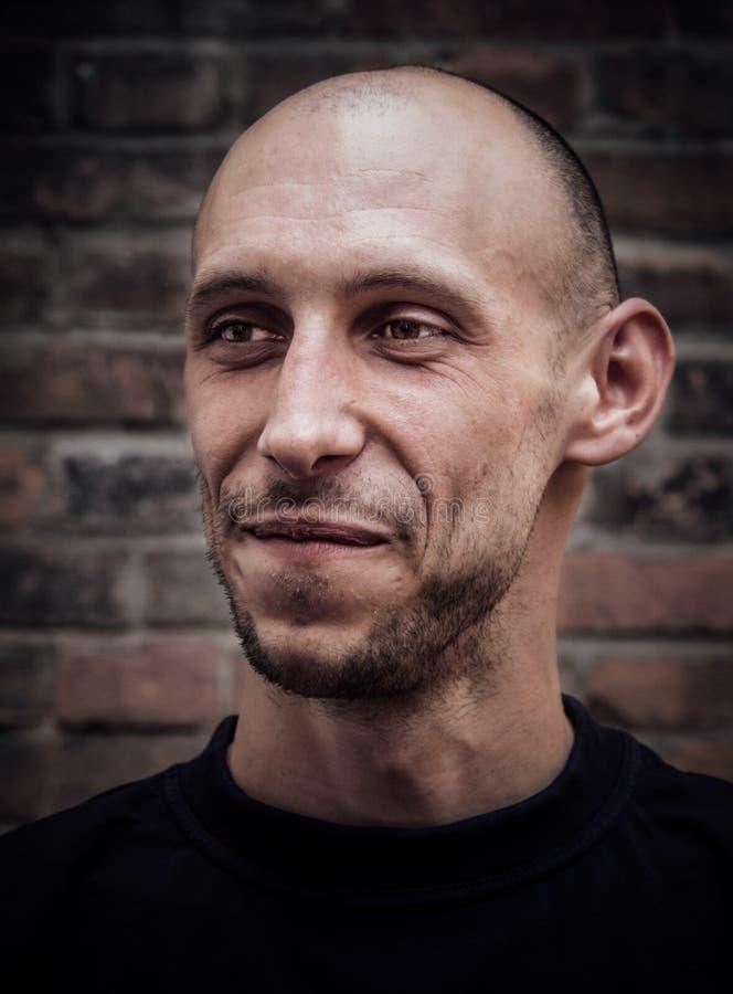 Nahaufnahmeporträt eines kahlen Mannes mit einem Lächeln und einem groben Auftritt stockbild
