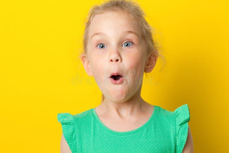 Nahaufnahmeporträt eines kleinen erstaunlichen Mädchens mit blauen Augen und Öffnung mouth lizenzfreies stockfoto