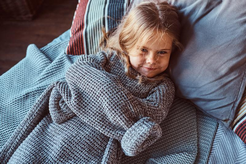 Nahaufnahmeporträt eines kleinen Mädchens in der warmen Strickjacke, die auf Bett liegt stockfotografie