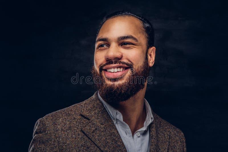 Nahaufnahmeporträt eines lächelnden hübschen bärtigen afro-amerikanischen Geschäftsmannes in einer braunen klassischen Jacke lizenzfreie stockfotos