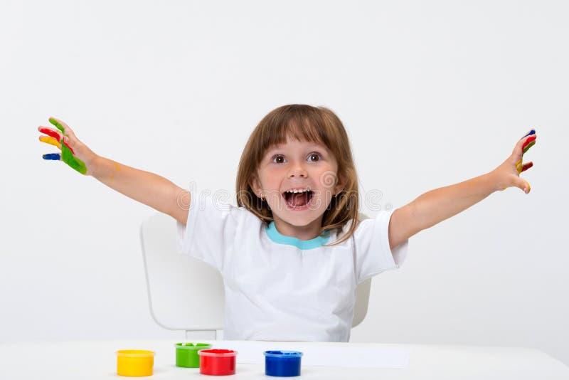 Nahaufnahmeporträt eines netten netten glücklichen lächelnden kleinen Mädchens zeichnet ihre eigenen Hände mit den Gouache- oder  lizenzfreie stockfotos