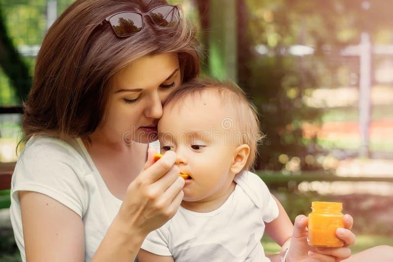 Nahaufnahmeporträt eines Säuglingsbabys, das Gemüsepüree vom Löffel isst Mutter, die das kleine Kind im Freien auf einem Weg am S lizenzfreie stockfotos