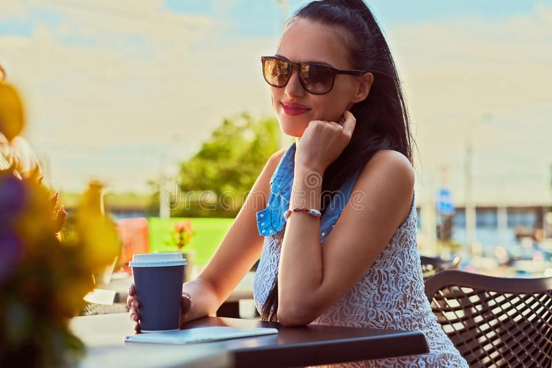 Nahaufnahmeporträt eines schönen Brunettefrauenmädchens, das modische Kleidung trägt, genießt Sommertag beim Sitzen auf a stockbild