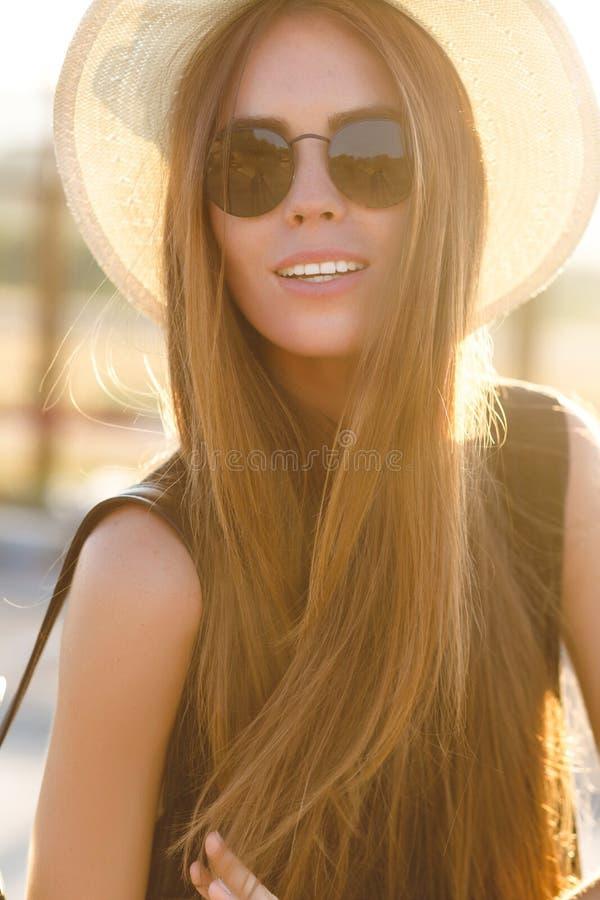 Nahaufnahmeporträt eines schönen jungen Mädchens mit langem tragendem Strohhut des dunklen Haares, dunkle Sonnenbrille Sie spielt stockbilder