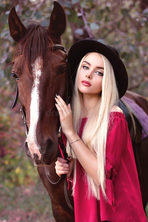 Nahaufnahmeporträt eines schönen kaukasischen Mädchens, das ein Pferd hält lizenzfreies stockbild