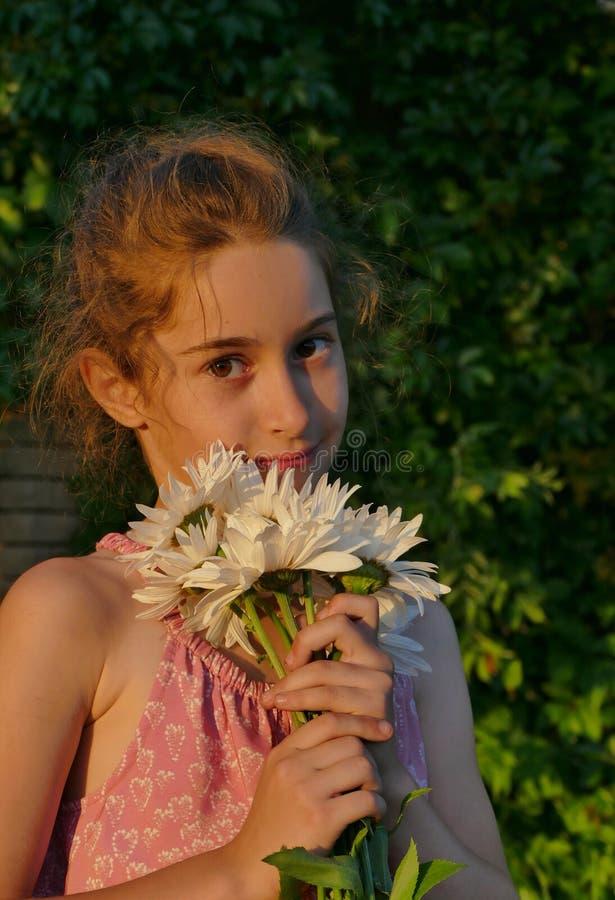 Nahaufnahmeporträt eines schönen kleinen Mädchens mit Blumen - Kamille lizenzfreie stockbilder