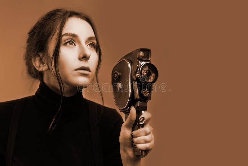 Nahaufnahmeporträt eines stilvollen jungen Mädchens, das eine alte Weinlesefilm novie Kamera im Schwarzweiss-Sepiaton hält stockfoto