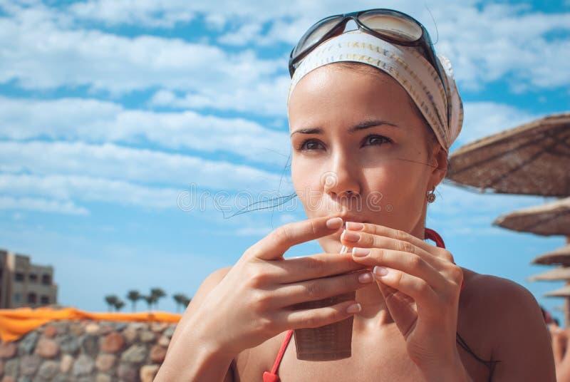 Nahaufnahmeporträt eines trinkenden Kaffees des jungen schönen Mädchens auf dem Strand, vor dem hintergrund der Sonnenschirme, Bl stockfotografie