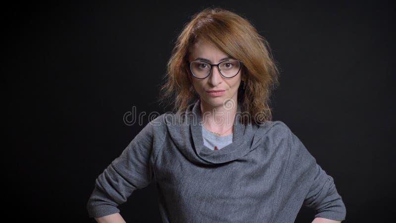 Nahaufnahmeporträt extravaganten Rothaarigefrau der von mittlerem Alter in den Gläsern, die Hände auf den Hüften haben und das We lizenzfreies stockbild