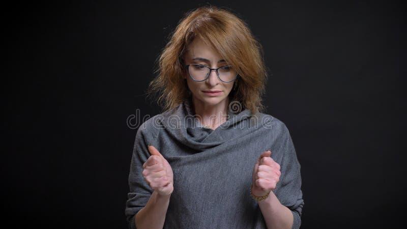 Nahaufnahmeporträt extravaganten Rothaarigen der von mittlerem Alter weiblich in den Gläsern, die besorgt und ihre Fäuste herein  lizenzfreie stockbilder