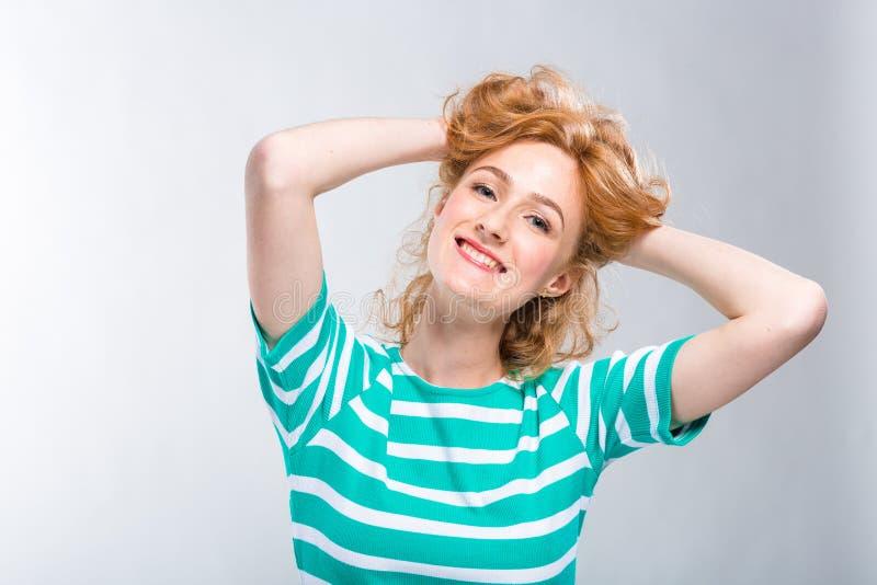 Nahaufnahmeporträt Junge, Schönheit mit dem roten gelockten Haar in einem Sommerkleid mit Streifen des Blaus im Studio auf einem  lizenzfreie stockfotografie