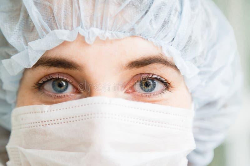Nahaufnahmeporträt jungen weiblichen Chirurgdoktors oder der tragenden Schutzmaske und des Hutes des Internierten lizenzfreies stockfoto