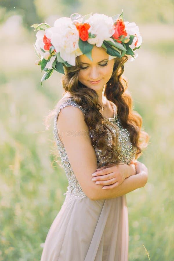 Nahaufnahmeporträt schöner reizend junger Dame im Blumenkranz und weißes Veilchen kleiden unten schauen lizenzfreie stockfotografie
