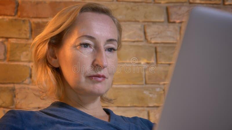 Nahaufnahmeporträt starker älterer kaukasischer Dame, die aufmerksam mit Laptop in der gemütlichen Hauptatmosphäre arbeitet stockbilder