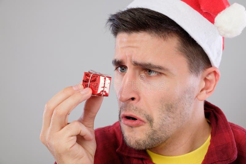 Nahaufnahmeporträt unglücklich, umgekippter Mann, der kleines rotes Geschenk hält stockfoto