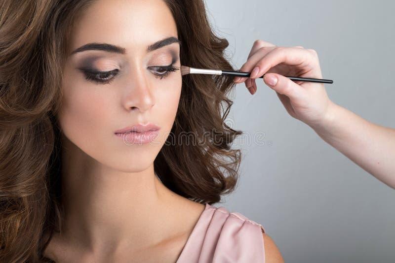 Nahaufnahmeporträt von Brunette beim Anwenden des Makes-up stockfotos