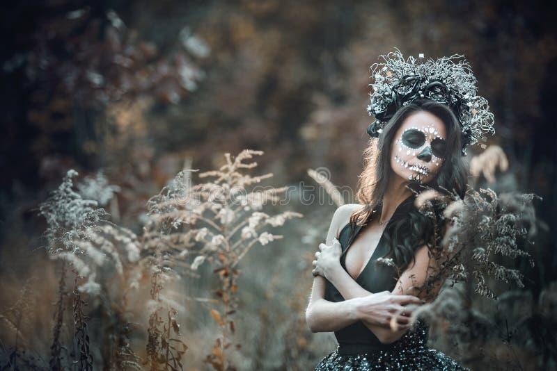 Nahaufnahmeporträt von Calavera Catrina im schwarzen Kleid Zuckerschädelmake-up Dia De Los Muertos Tag der Toten Halloween stockfotografie