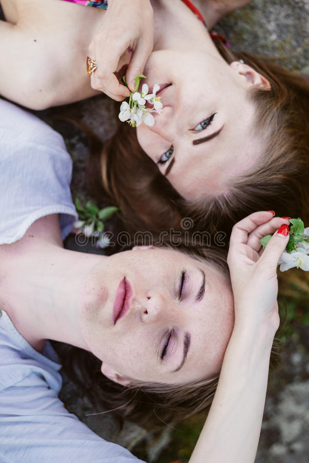 Nahaufnahmeporträt von den liegenden Kopf-an-Kopf- glücklichen Freundinnen, die das glückliche Lächeln sich entspannen stockfotos