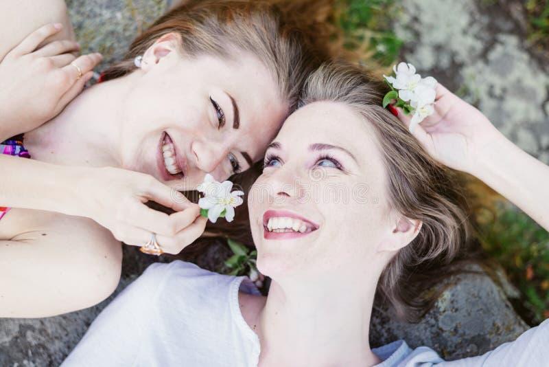 Nahaufnahmeporträt von den liegenden Kopf-an-Kopf- glücklichen Freundinnen, die das glückliche Lächeln sich entspannen lizenzfreies stockfoto