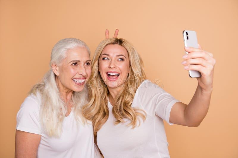 Nahaufnahmeporträt von den netten reizenden attraktiven reizend netten netten heitren spielerischen komischen Damen, die weißes T stockfoto