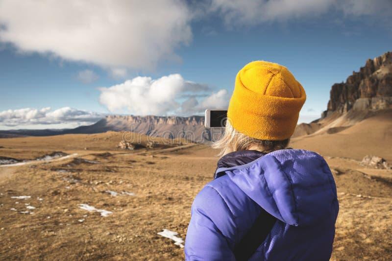 Nahaufnahmeporträt von der Rückseite eines reisenden Mädchens in einer unten Jacke mit einer Kappe, die Fotos einer epischen Land stockfotografie