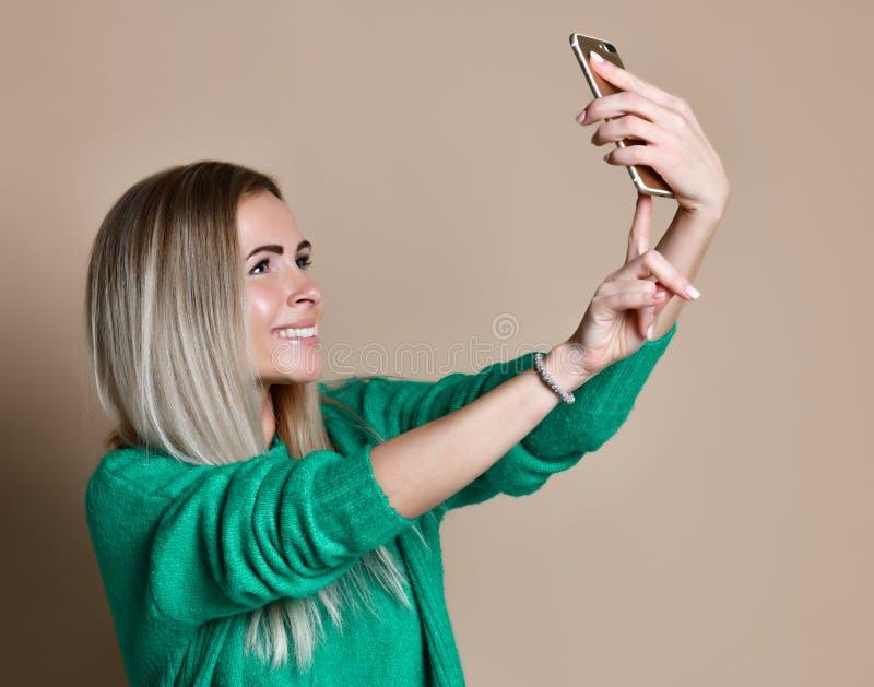 Nahaufnahmeporträt von jungen netten Modeblondinen in der Strickjackenabnutzung macht selfie auf Smartphone stockfotografie