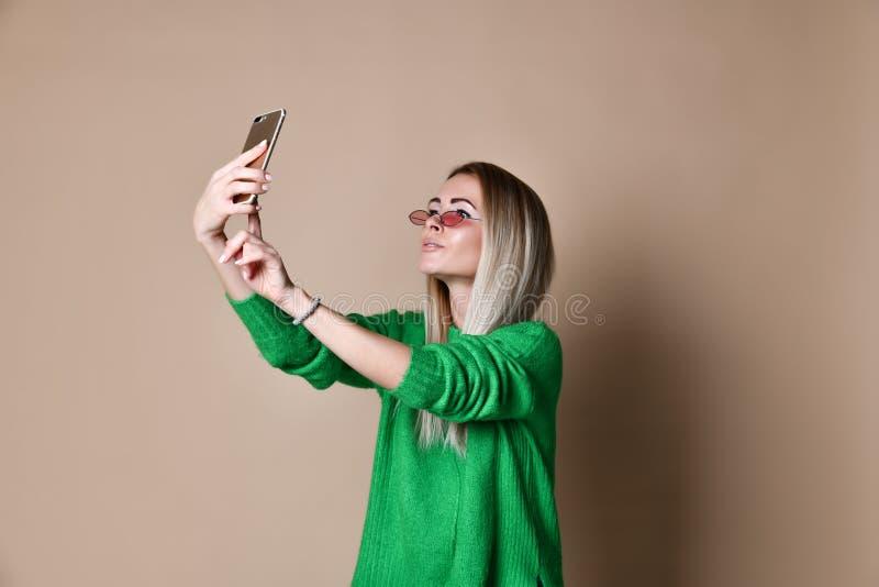 Nahaufnahmeporträt von jungen netten Modeblondinen in der Strickjackenabnutzung macht selfie auf Smartphone, über beige Hintergru stockbild