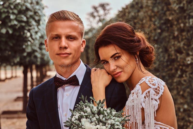 Nahaufnahmeporträt von Jungvermählten - reizend Braut legte ihren Kopf auf ihren hübschen Bräutigam in einem Park stockbilder