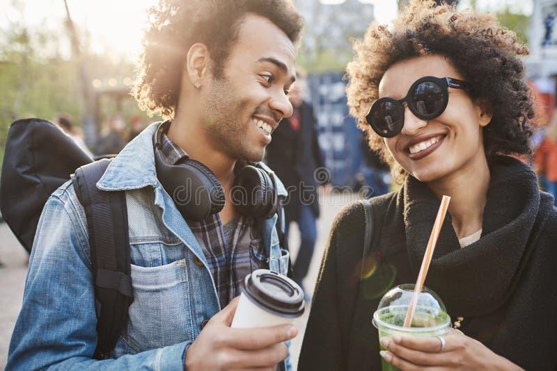 Nahaufnahmeporträt von netten jungen Paaren von den Liebhabern, die Getränke halten und miteinander beim Gehen in Park lächeln un stockbild