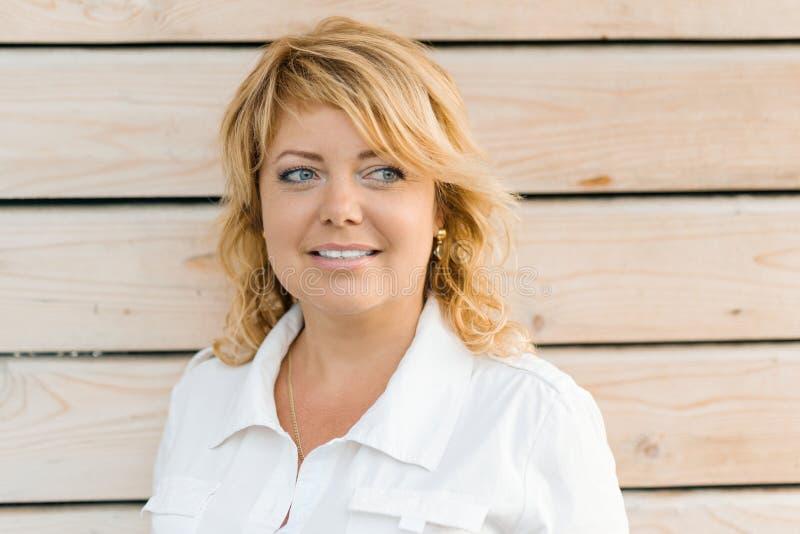 Nahaufnahmeporträt von reifen Blondinen von mittlerem Alter Hölzerner Hintergrund im Freien, weibliches Lächeln lizenzfreie stockfotografie
