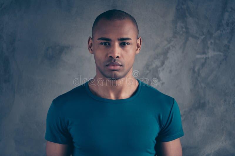 Nahaufnahmeporträt von seinem er netter attraktiver gekümmerter ruhiger offener Kerl, der zufälliges blaues T-Shirt über grauer B stockfoto