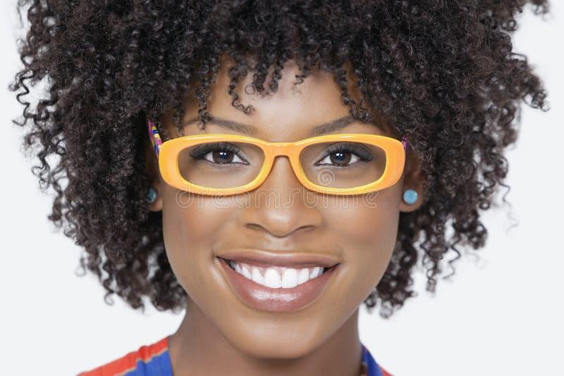 Nahaufnahmeporträt von tragenden Gläsern einer Afroamerikanerfrau über grauem Hintergrund stockfoto