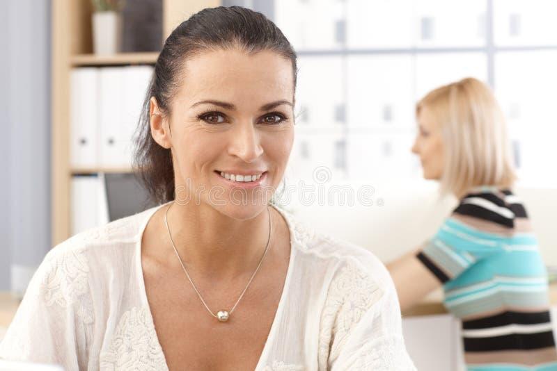 Nahaufnahmeporträt zufälligen glücklichen Bürosekretärs lizenzfreie stockfotos