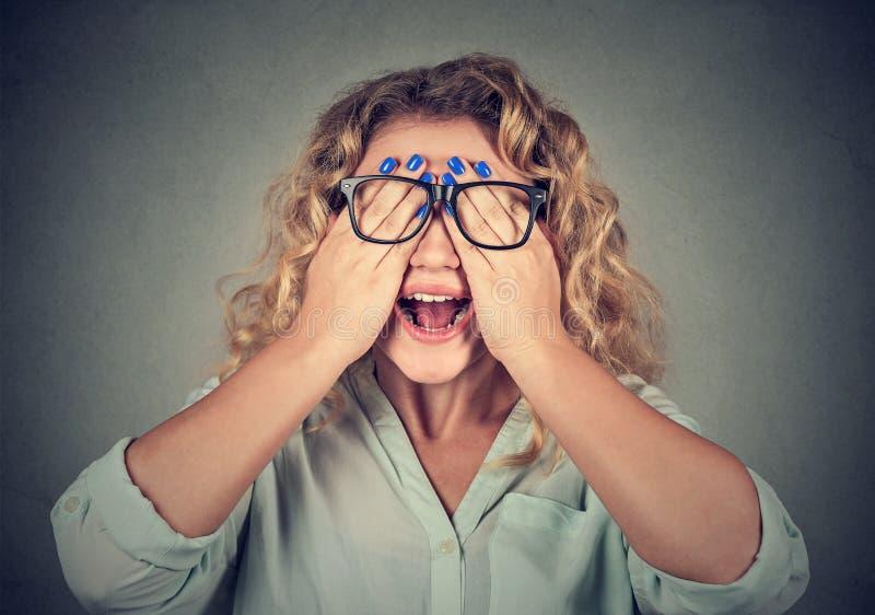 Nahaufnahmeporträtfrau in den Gläsern, die Gesicht bedecken, mustert mit beiden Händen stockfotografie